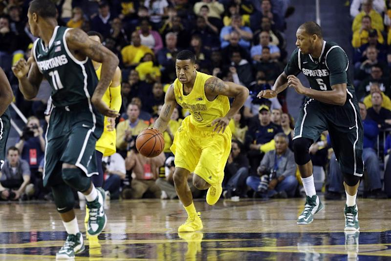 Michigan guard Trey Burke (3) dribbles upcourt during the first half of an NCAA college basketball game against Michigan State in Ann Arbor, Mich., Sunday, March 3, 2013. (AP Photo/Carlos Osorio)