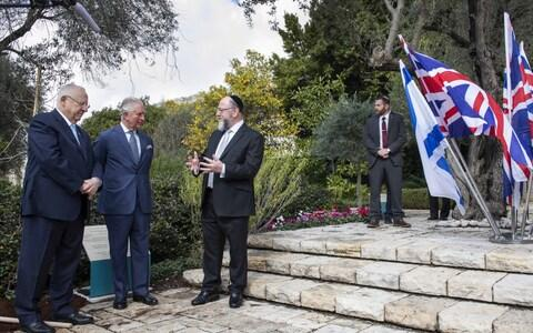 Charles plants a tree in the grounds of the official residence of Israeli President Reuven Rivlin watched on by Chief Rabbi Ephraim Mirvis - Credit: Getty