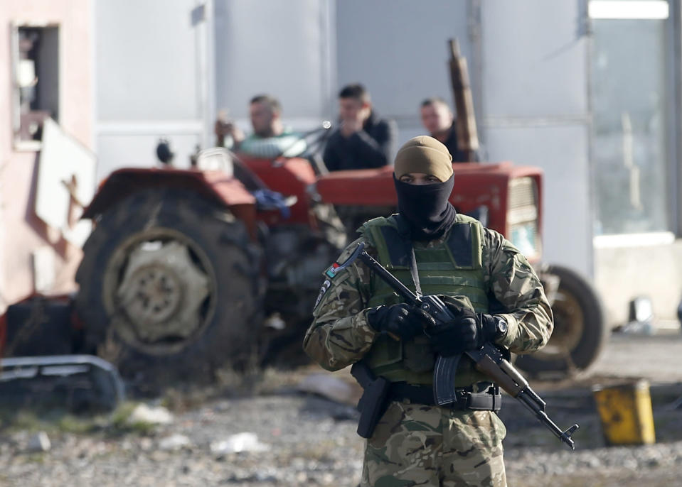 A soldier of NATO-led peacekeeping force KFOR guards convoy of the road near the village of Leposavic, northern Kosovo, Thursday, Dec. 13, 2018. In Friday's vote, Kosovo's 120-seat parliament is expected to approve three draft laws to turn an existing paramilitary force into a lightly armed army. (AP Photo/Darko Vojinovic)