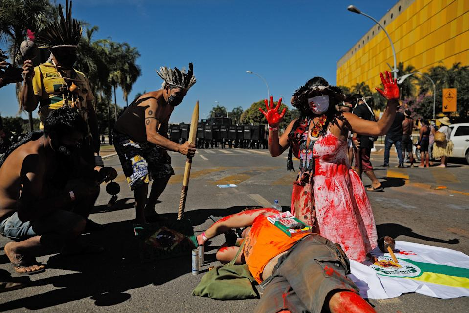 Indigenous people make a performance in front of a line of riot police during a protest outside the National Congress in Brasilia, on June 22, 2021. - Indigenous people are camping in the capital to oppose a bill said to limit recognition of reserve lands. (Photo by Sergio Lima / AFP) (Photo by SERGIO LIMA/AFP via Getty Images)