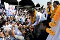 Palang Pracharat party leader Uttama Savanayana (R) is greeted by supporters during a campaign rally in Narathiwat