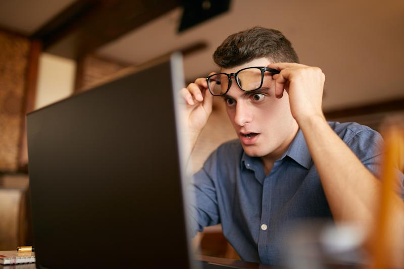 Shocked freelancer hipster man looks to laptop screen and can not believe unpleasant news. Pop-eyed frightened businessman trader raises one's glasses above his eyes. Trader monitoring stock exchange market.