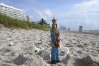 A statue sits on the beach with candles and flower petals near the Champlain Towers South Condo building, Saturday, June 26, 2021, in the Surfside area of Miami. The apartment building partially collapsed on Thursday. (AP Photo/Lynne Sladky)