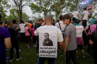 """A supporter of the anti-military Future Forward Party wears a T-shirt with a portrait of Thai Prime Minister Prayuth Chan-ocha during a run dubbed as """"Run Against Dictatorship"""" at a park in Bangkok, Thailand, Sunday, Jan. 12, 2020. Writing on the costume reads as """"I was born under Prayuth Government, severely poor."""" (AP Photo/Gemunu Amarasinghe)"""