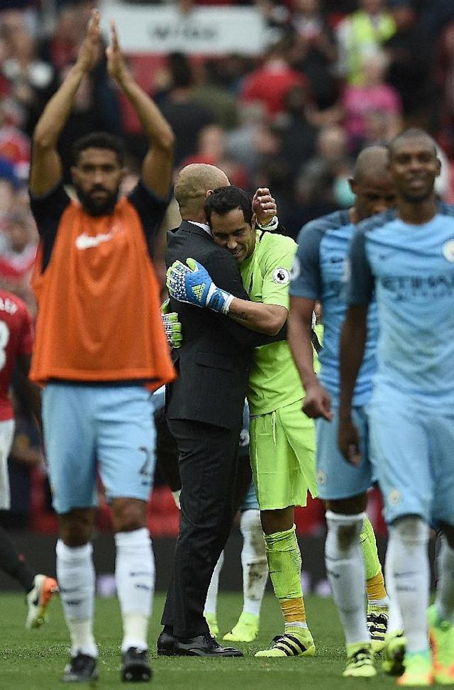 Manchester City's manager Pep Guardiola embraces goalkeeper Claudio Bravo as they celebrate after defeating Manchester United in their English Premier League match, at Old Trafford, on September 10, 2016 (AFP Photo/Oli Scarff)