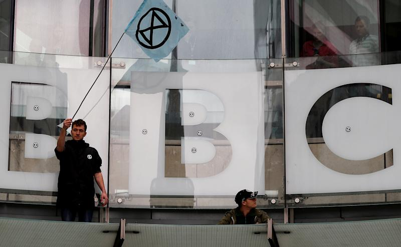A protester waves a flag next to the BBC logo at the company's headquarters during an Extinction Rebellion demonstration in London, Britain October 11, 2019. REUTERS/Peter Nicholls