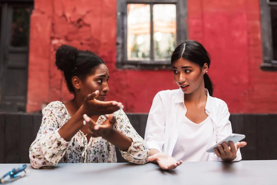 young black and asian women arguing outdoors in front of red building