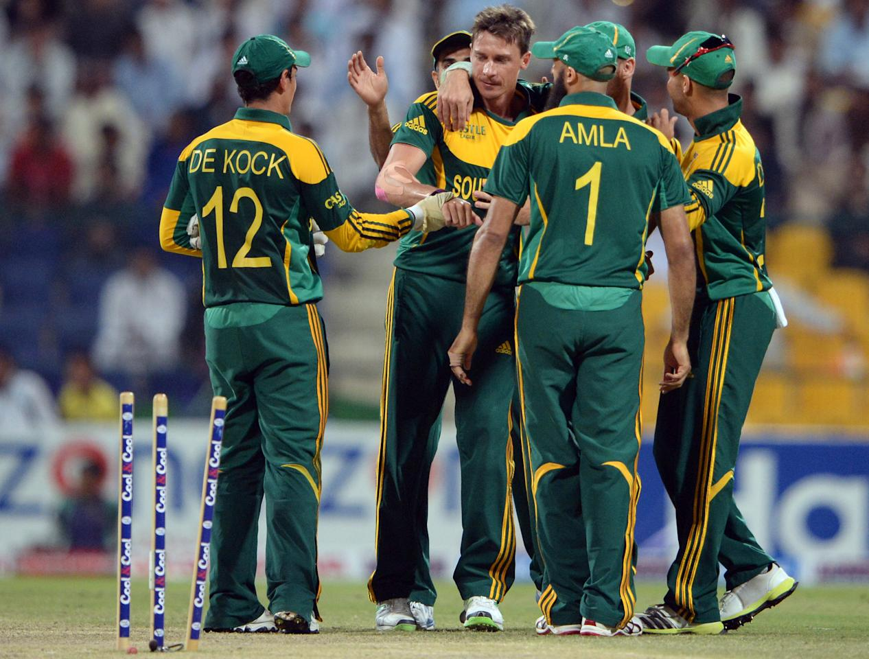 South African bowler Dale Steyn (C) celebrates with teammates after clean bowled of Pakistani cricketer Saeed Ajmal (unseen) during the fourth day-night international in Sheikh Zayed Cricket Stadium in Abu Dhabi on November 8, 2013. South Africa beat Pakistan by 28 runs, to take an unbeatable 3-1 lead in the five-match series. AFP PHOTO/ ASIF HASSAN        (Photo credit should read ASIF HASSAN/AFP/Getty Images)