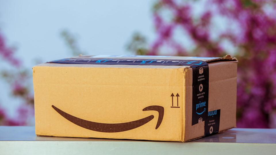 PARIS, FRANCE - APR 19, 2018: Delivered Amazon Cardboard box left outdoor the house by courier with large Amazon Smile logotype against defocused tree background.