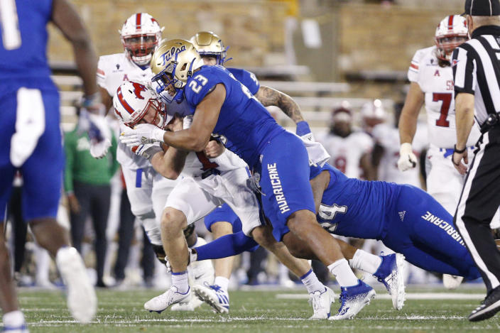 FILE - SMU quarterback Shane Buechele (7) is stopped short of a first down by Tulsa linebacker Zaven Collins (23) during the second half of an NCAA college football game in Tulsa, Okla., in this Saturday, Nov. 14, 2020, file photo. Zaven Collins is a small-town player with big-time talent. He was overlooked after a stellar high school career in Hominy, Okla., a town with about 3,500 people. He's got the nation's attention now -- the 6-foot-4, 260-pound linebacker is a finalist for the Butkus and Nagurski Awards. (AP Photo/Joey Johnson, File)