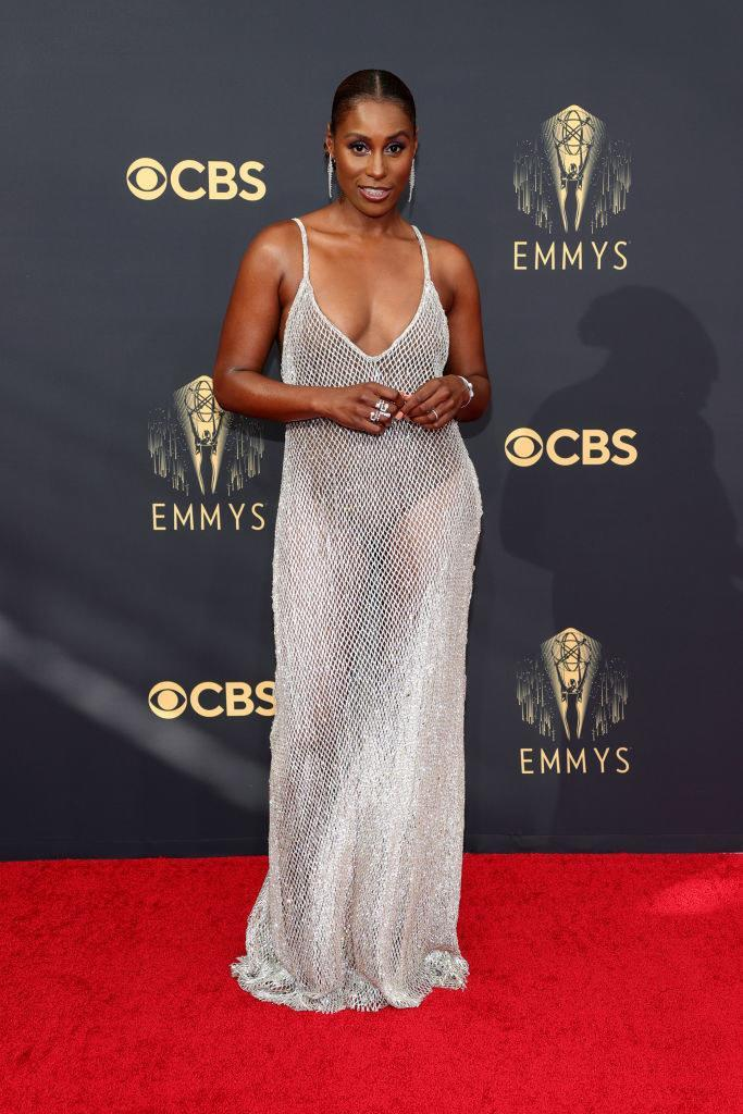 Issa Rae on the red carpet in a silver gown