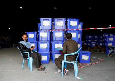 Afghan election commission workers sit next to ballot boxes and election material at a warehouse in Kabul