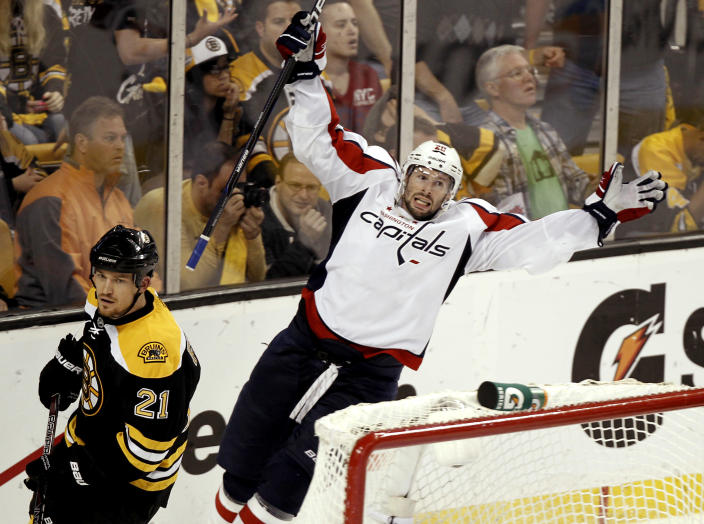 Washington Capitals' Troy Brouwer celebrates his winning goal as Boston Bruins defenseman Andrew Ference (21) skates away during the third period of Washington's 4-3 win in Game 5 in a first-round NHL Stanley Cup playoff hockey series in Boston Saturday, April 21, 2012. (AP Photo/Winslow Townson)