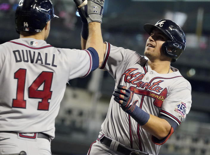 CORRECTS TO AUSTIN RILEY NOT FREDDIE FREEMAN - Atlanta Braves' Austin Riley, right, gets a high-five from Adam Duvall (14) after hitting a two-run home run against the Arizona Diamondbacks during the third inning of a baseball game Thursday, Sept 23, 2021, in Phoenix. (AP Photo/Darryl Webb)
