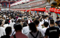 "People wearing face masks pack in a shopping arcade of Asakusa district in Tokyo Sunday, Sept. 20, 2020. Train stations and airports in Japan are filled with people traveling over the ""Silver Week"" holiday weekend, in a sign of recovery amid the coronavirus pandemic. (Kyodo News via AP)"