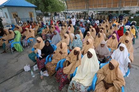 Some of the newly released Dapchi schoolgirls wait for boarding a plane at the air force base in Maiduguri