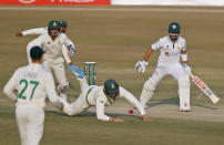 Pakistan's Mohammad Rizwan, right, looks to South Africa's Rassie van der Dussen, center, dropping his catch during the third day of the second cricket test match between Pakistan and South Africa at the Pindi Stadium in Rawalpindi, Pakistan, Saturday, Feb. 6, 2021. (AP Photo/Anjum Naveed)
