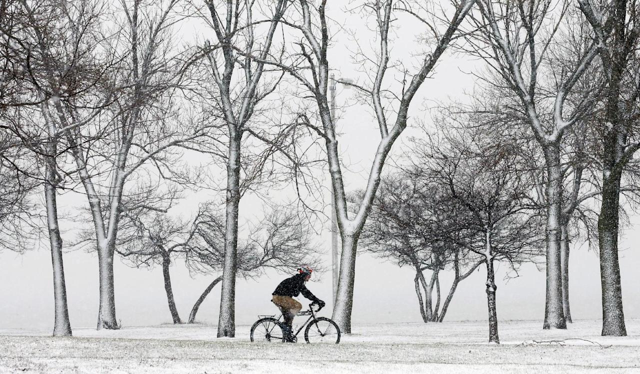 A lone cyclist navigates the bike path through a snow storm at Chicago's North Ave. beach Thursday, Dec. 27, 2012. A muted version of the deadly winter storm that has killed more than a dozen across the eastern half of the country reached the Northeast on Thursday, limiting most of its wrath to travel headaches as Christmas revelers tried to return home.  (AP Photo/Charles Rex Arbogast)