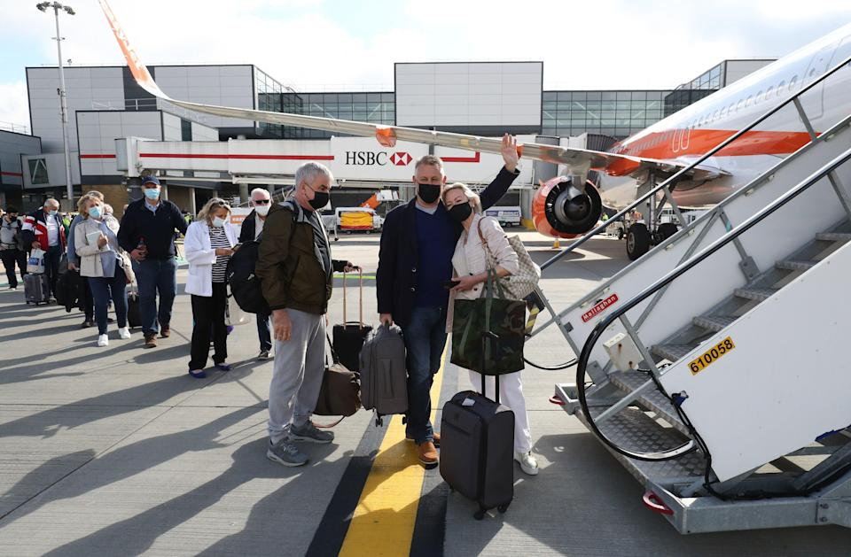 Passengers prepare to board an easyJet flight to Faro, Portugal, at Gatwick Airport (PA)
