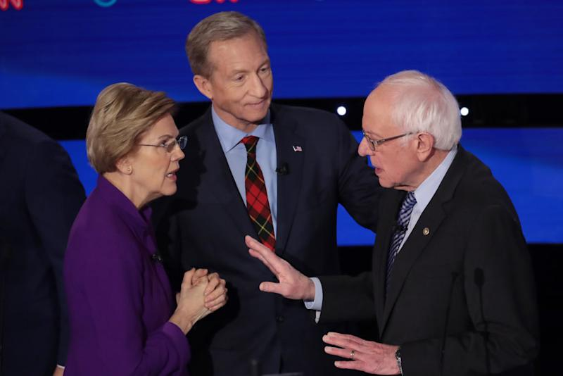 Elizabeth Warren and Bernie Sanders shown speaking to each other as Tom Steyer looks on after the Democratic presidential primary debate.