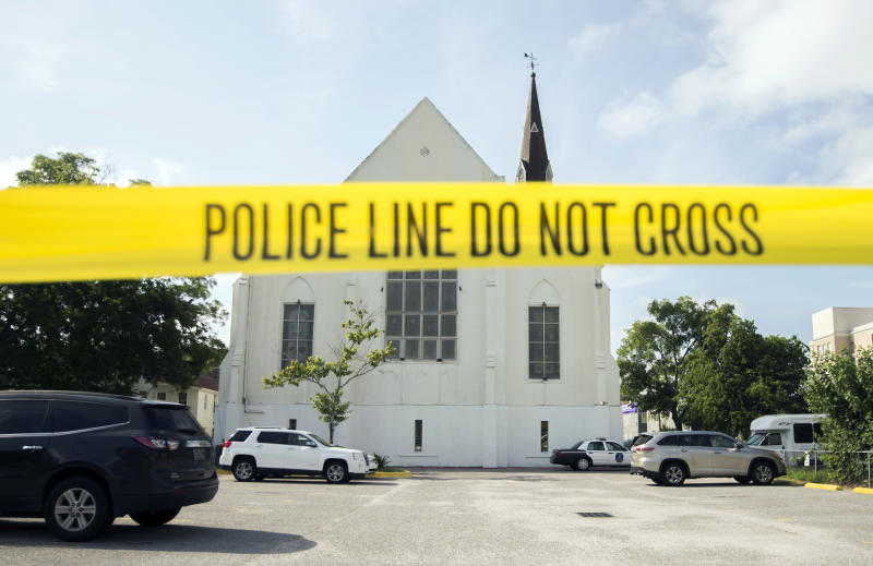 """FILE - In this June 19, 2015 file photo, police tape surrounds the parking lot behind the AME Emanuel Church as FBI forensic experts work the crime scene, in Charleston, S.C. he new documentary, """"Emanuel,"""" explores life after the tragic shooting took place on June 17, 2015, as family members, friends and the community try to heal through faith and forgiveness. (AP Photo/Stephen B. Morton, File)"""
