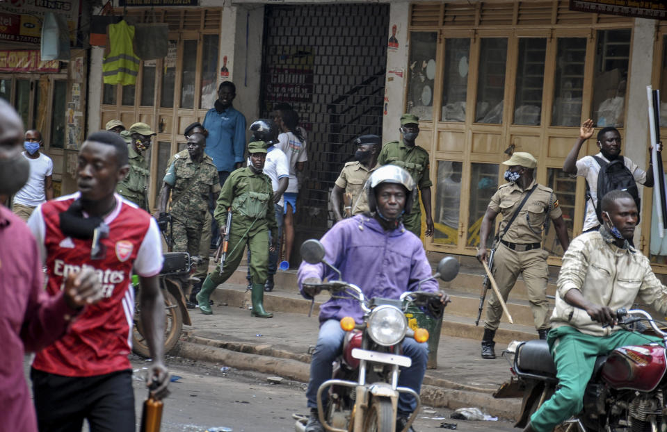 """FILE - In this Thursday, Nov. 19, 2020 file photo, Ugandan security forces patrol on a street after protests over the arrest of opposition presidential candidate Bobi Wine, in Kampala, Uganda. The United States said Friday, April 16, 2021 that it is imposing visa restrictions on """"those believed to be responsible for, or complicit in, undermining the democratic process in Uganda,"""" including during the election in January and the campaign period. (AP Photo, File)"""
