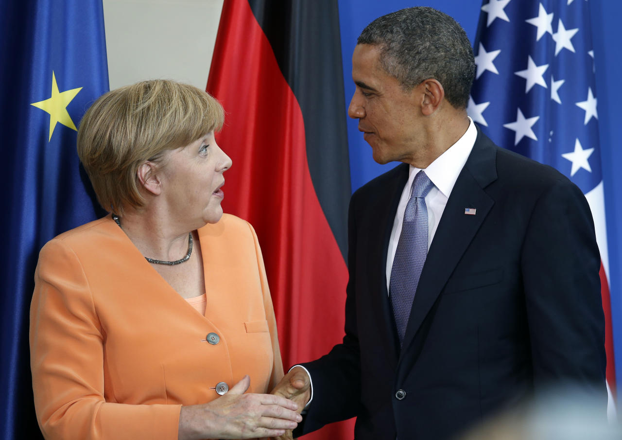 US President Barack Obama, right, and German Chancellor Angela Merkel, left, shake hands after a joint press conference at the chancellery in Berlin Wednesday, June 19, 2013. On the second day of his visit to Germany Obama met with German President Joachim Gauck and Chancellor Merkel before delivering a speech at Brandenburg Gate. (AP Photo/Michael Sohn)