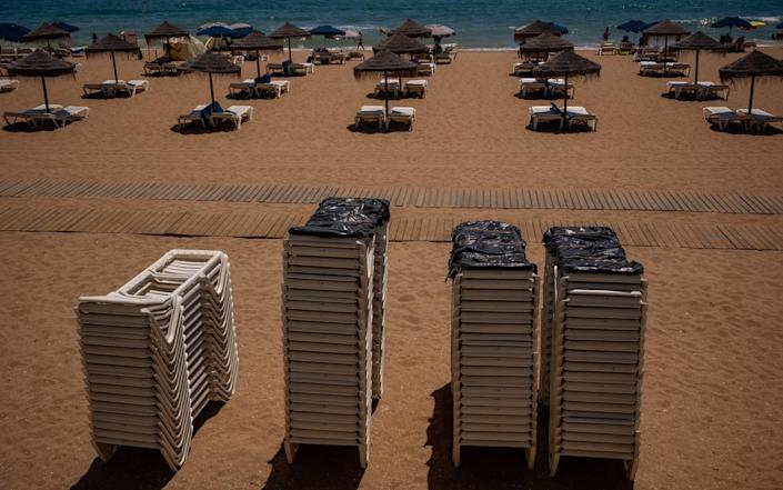 More empty sun loungers sit stacked on Albufeira beach - BLOOMBERG