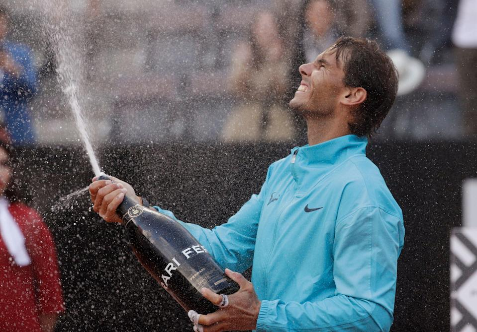 Rafael Nadal of Spain celebrates with sparkling wine after winning against Novak Djokovic of Serbia at the end of their final match at the Italian Open tennis tournament, in Rome, Sunday, May 19, 2019. (AP Photo/Gregorio Borgia)