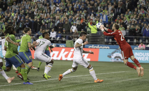Seattle Sounders goalkeeper Stefan Frei, right, pushes out a ball as Portland Timbers defender Liam Ridgewell, second from left, closes in, during the first half of the second leg of an MLS soccer playoff series Thursday, Nov. 8, 2018, in Seattle. (AP Photo/Ted S. Warren)