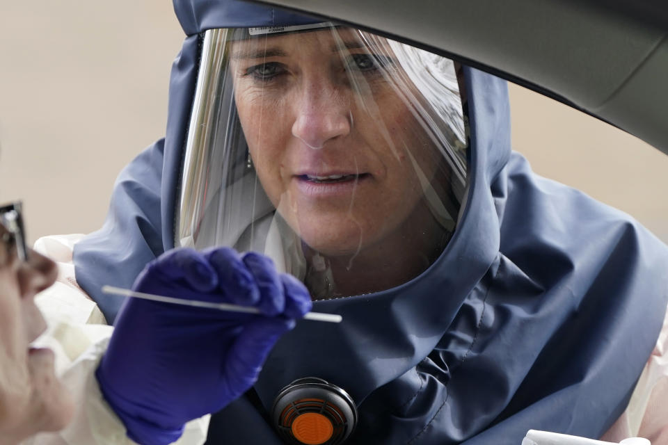 "Salt Lake County Health Department public health nurse Lee Cherie Booth performs a coronavirus test outside the Salt Lake County Health Department on Friday, Oct. 23, 2020, in Salt Lake City. Utah hit another ominous record by tallying the highest number of confirmed coronavirus cases in a single day as the state struggles to slow a monthlong surge of COVID-19 that is filling intensive care beds at hospitals. Gov. Gary Herbert warned in a statement that the state is ""on the brink,"" and once again pleaded with people to adhere to mask mandates in place in most counties in the state. (AP Photo/Rick Bowmer)"