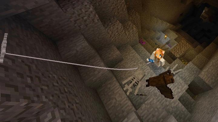 A minecraft character uses a grappling hook to climb out of the underground
