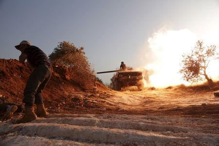 A rebel fighter of the Al-Furqan brigade covers his ears as a fellow fighter fires a vehicle's weapon during what the rebels said is an offensive to take control of the al-Mastouma army base which is controlled by forces loyal to Syria's President Bashar al-Assad near Idlib city May 17, 2015. REUTERS/Khalil Ashawi