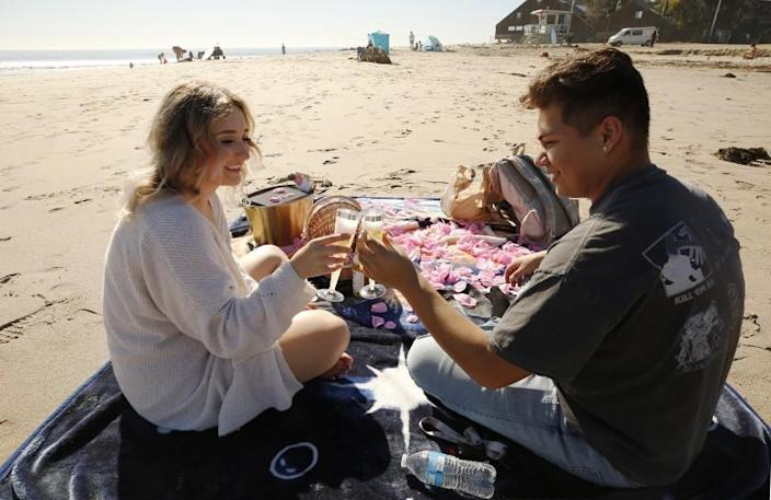 MALIBU, CA - JANUARY 14: Abigail Pimentel, 18, from Fresno and boyfriend Daniel Diaz, 18, from LA who surprised her with a lunch basket, sparkling apple cider and a spread of flower petals on a beach blanket, as they couple celebrate their anniversary at Malibu Lagoon State Beach on Thursday as temps got into the 80's and Santa Ana winds return to the Southland this week, bringing warm winter weather with gusty and dry conditions, raising the risk of wildfires. Malibu Lagoon State Beach on Thursday, Jan. 14, 2021 in Malibu, CA. (Al Seib / Los Angeles Times)