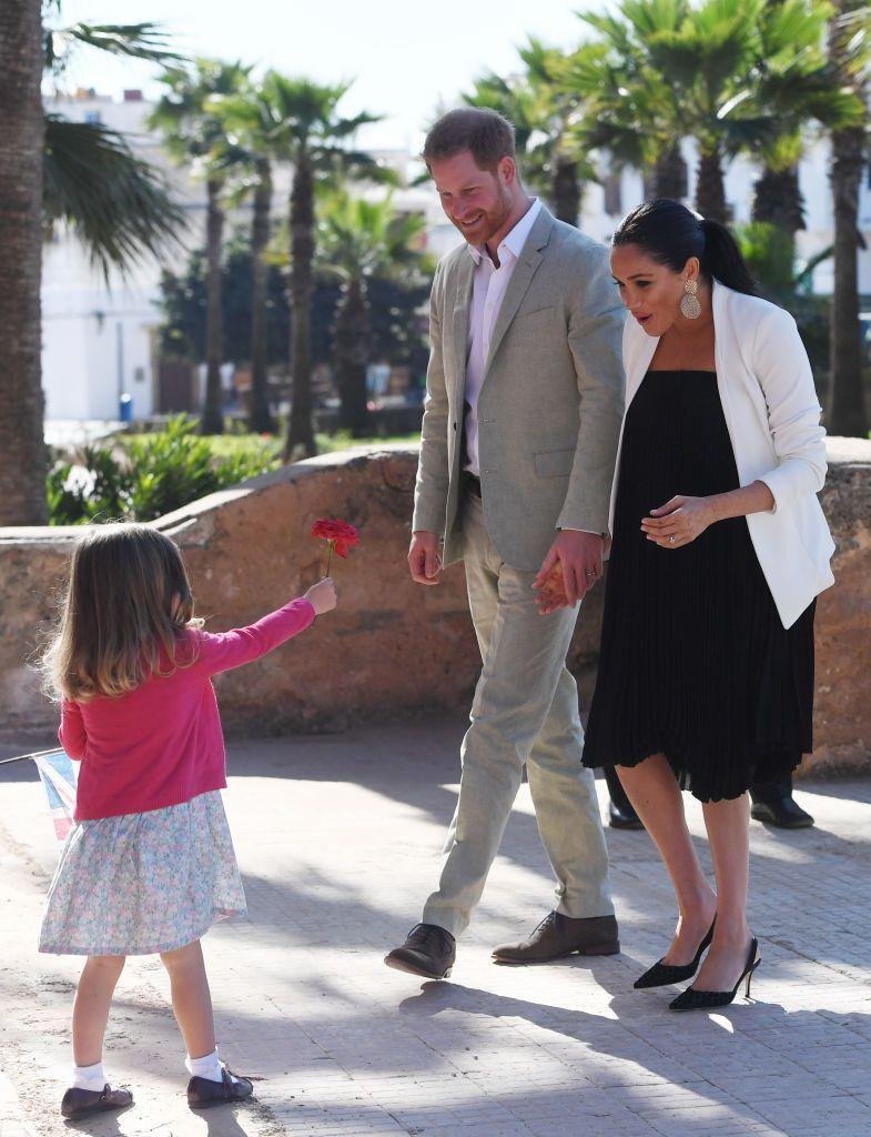 "<p>The Sussexs appear elated as they meet a young girl who offers them a flower during their walkabout in the Andalusian Gardens in Rabat. </p><p><strong>More: </strong><a href=""https://www.townandcountrymag.com/style/fashion-trends/g3272/meghan-markle-preppy-style/"" rel=""nofollow noopener"" target=""_blank"" data-ylk=""slk:Meghan Markle's Style Evolution"" class=""link rapid-noclick-resp"">Meghan Markle's Style Evolution</a></p>"