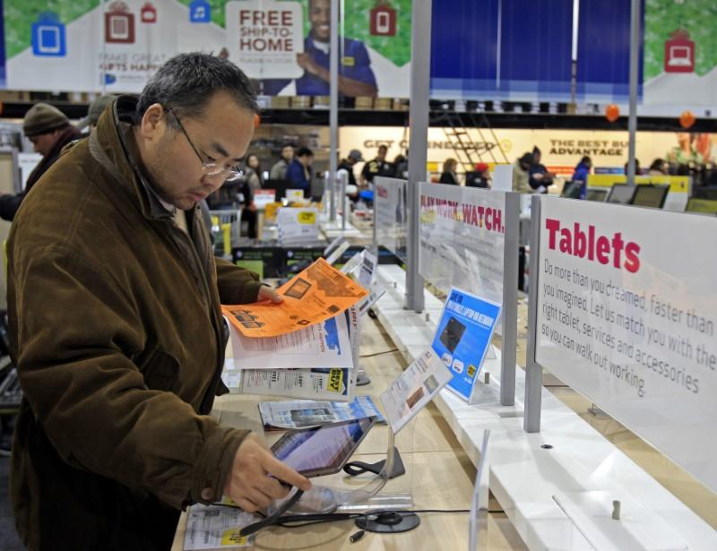 "A shopper looks at tablet computers at a Best Buy Store on the shopping day dubbed ""Black Friday"" in Framingham"