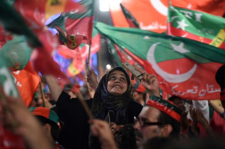 Pakistan Tehreek-e-Insaf supporters wave party flags during campaigning that brought Imran Khan to power in July 2018