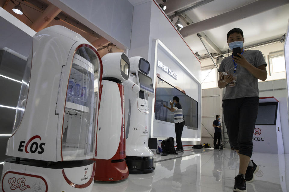 Workers prepare a display near robots at the China International Fair for Trade in Services (CIFTIS) to be held in Beijing on Friday, Sept. 4, 2020. As China recovers from the COVID-19 pandemic, business as usual is picking back up with the holding of the China International Fair for Trade in Services. Nearly 2,000 Chinese and foreign enterprises will participate and showcase their newest technology in public health and digital technology (AP Photo/Ng Han Guan)