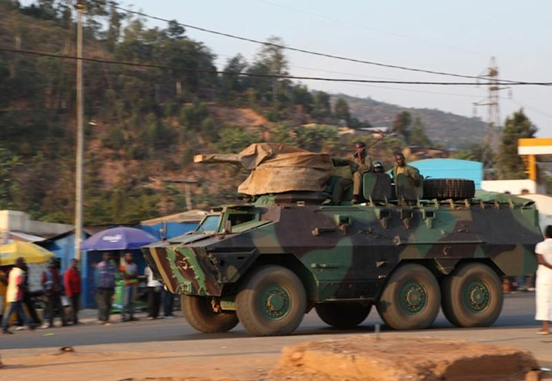 CORRECTS DATE - A Rwandan armored vehicle with soldiers on top drives past residents of Kigali, Rwanda Friday Aug. 30, 2013 as it heads towards western border. Rwandan forces on Friday continued to deploy on the border with Democratic Republic of Congo (DRC) after the central African country said it 'could not tolerate' any more violations from its vast neighbour to the west. Trucks carrying heavy artillery and armored tanks started living Kigali on Thursday night a few hours after Rwanda's Minister of Foreign Affairs Louise Mushikiwabo said that her country will move to defend her borders after bombs allegedly from the DRC side fell in the western town of Gisenyi, killing two. (AP Photo)