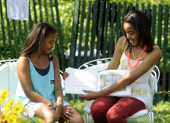 Sasha Obama and Malia Obama read to children during the White House Easter Egg Roll on the South Lawn of the White House on April 25, 2011 in Washington, DC. About 30,000 people are expected to attend the 133-year-old tradition of rolling colored eggs down the White House lawn. (Photo by Roger L. Wollenberg-Pool/Getty Images)