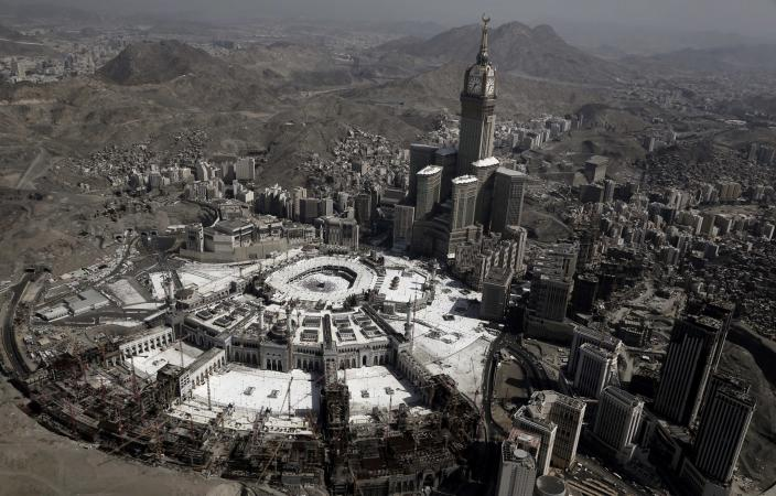 FILE - In this Sept. 13, 2016 file photo, the Abraj Al-Bait Towers with the four-faced clocks stands over the holy Kaaba, as Muslims encircle it inside the Grand Mosque, during the hajj pilgrimage, in Mecca, Saudi Arabia. Over 2 million Muslims from around the world are beginning the five-day hajj pilgrimage on Friday, Aug, 8, 2019. They will take part in a series of rituals intended to bring about greater humility and unity among Muslims. (AP Photo/Nariman El-Mofty, File)