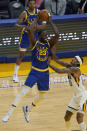 Golden State Warriors forward Draymond Green, center, is defended by Utah Jazz guard Jordan Clarkson, right, during the first half of an NBA basketball game in San Francisco, Monday, May 10, 2021. (AP Photo/Jeff Chiu)
