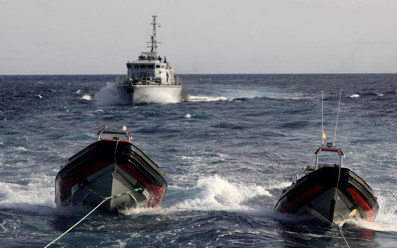 A Libyan coastguard vessel chases away former fishing trawler Golf Azzurro of the Proactiva Open Arms rescue charity in the Western Mediterranean Sea - REUTERS