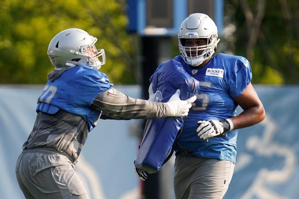 Lions offensive tackle Penei Sewell, left, runs a drill with Tyrell Crosby during training camp practice in Allen Park on Saturday, July 31, 2021.