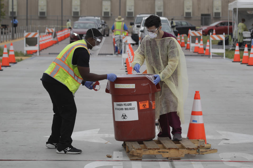 Workers collect samples at a mobile Coronavirus testing site at the Charles Drew University of Medicine and Science Wednesday, July 22, 2020, in Los Angeles. California's confirmed coronavirus cases have topped 409,000, surpassing New York for most in the nation. (AP Photo/Marcio Jose Sanchez)