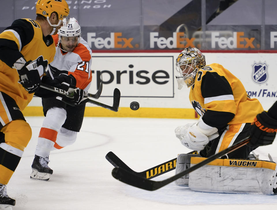 Pittsburgh Penguins goaltender Tristan Jarry (35) watches the puck off the stick of Philadelphia Flyers' Scott Laughton (21) during the second period of an NHL hockey game Thursday, March 4, 2021, in Pittsburgh. (AP Photo/Keith Srakocic)