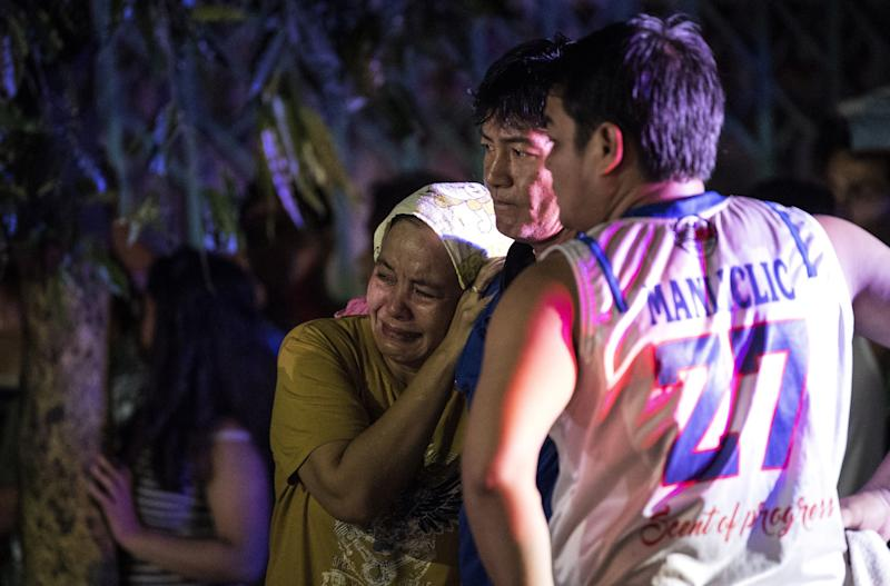 Relatives of Aldrin Castillo, an alleged drug user killed by unidentified assailants, grieve as they arrive at the crime scene in Manila on Oct. 3, 2017.