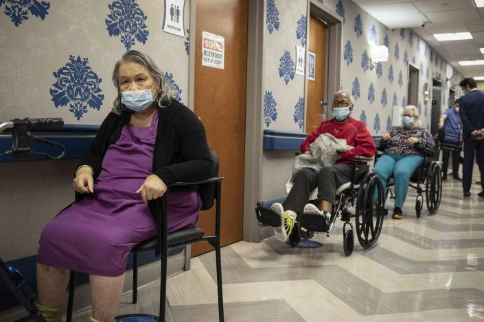 FILE - In this Friday, Jan. 15, 2021 file photo, nursing home residents wait on line to receive a COVID-19 vaccine at Harlem Center for Nursing and Rehabilitation in the Harlem neighborhood of New York. The Justice Department says it's decided against opening up any civil rights investigations against government-run nursing homes in New York over their COVID-19 response, in a letter to members of U.S. Congress, Friday, July 23, 2021. (AP Photo/Yuki Iwamura, File)