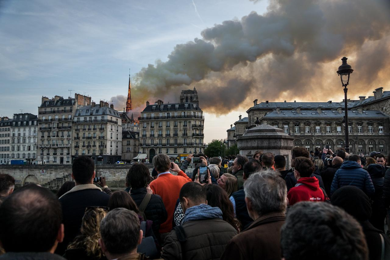 <p>People watch the landmark Notre Dame Cathedral burning in central Paris on April 15, 2019 (Photo by Nicolas Liponne/NurPhoto via Getty Images) </p>