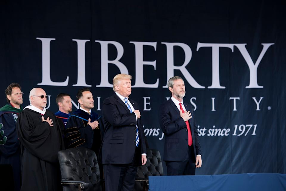 President Donald Trump and Jerry Falwell Jr. (right) participate in the Pledge of Allegiance during Liberty University's commencement ceremony on May 13, 2017, in Lynchburg, Virginia. (Photo: BRENDAN SMIALOWSKI via Getty Images)